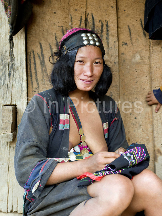 Portrait of an Akha Cherpia ethnic minority woman sewing traditional clothing outside her home in Ban Nam Hin village, Phongsaly Province, Lao PDR.  One of the most ethnically diverse countries in Southeast Asia, Laos has 49 officially recognised ethnic groups although there are many more self-identified and sub groups. These groups are distinguished by their own customs, beliefs and rituals. Details down to the embroidery on a shirt, the colour of the trim and the type of skirt all help signify the wearer's ethnic and clan affiliations.