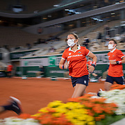 PARIS, FRANCE September 28.  Ball girls and ball boys swap positions between sets on Court Philippe-Chatrier in the first round of the singles competition during the  French Open Tennis Tournament at Roland Garros on September 28th 2020 in Paris, France. (Photo by Tim Clayton/Corbis via Getty Images)
