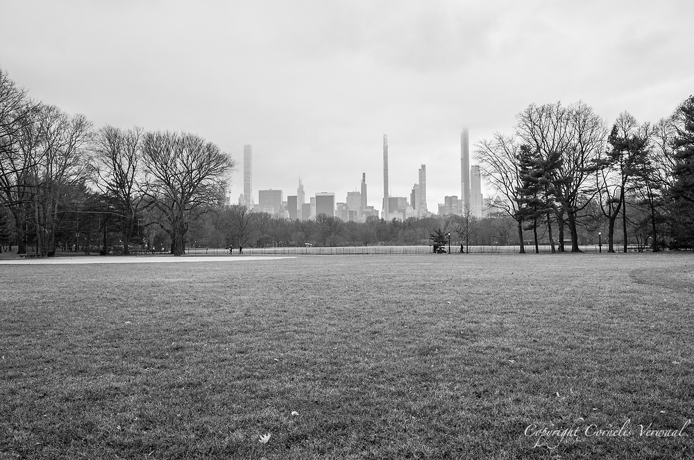 Competing skyscrapers of Mid-Manhattan disappearing into the clouds, seen over The Great Lawn in Central Park
