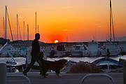 The harbour at sunset, boats moored at the key side, sun setting behind the mountains, a man in silhouette walking a dog Le Brusc Six Fours Var Cote d'Azur France