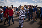"""Lesa Martino, a supporter of Republican presidential candidate Donald Trump,  wears a """"Hillary for prison"""" costume at a campaign rally at Lakeland Linder Regional Airport in Lakeland, Florida, October 12, 2016."""