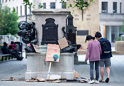 © Licensed to London News Pictures; 11/06/2020; Bristol, UK. People look at signs left at the now empty plinth where the statue of 17th century slave trader and Bristol philanthropist Edward Colston used to stand. At a Black Lives Matter protest the previous Sunday the statue of slave trader Edward Colston which has stood in Bristol city centre for over 100 years was pulled down with ropes and thrown in Bristol Docks by protesters during the BLM rally and march through the city centre in memory of George Floyd, a black man who was killed on May 25, 2020 in Minneapolis in the US by a white police officer kneeling on his neck for nearly 9 minutes. Edward Colston (1636 – 1721) was a wealthy Bristol-born English merchant involved in the slave trade, a Member of Parliament and a philanthropist. He supported and endowed schools, almshouses, hospitals and churches in Bristol, London and elsewhere, and his name is commemorated in several Bristol landmarks, streets, three schools and the Colston bun. The killing of George Floyd has seen widespread protests in the US, the UK and other countries. Photo credit: Simon Chapman/LNP.