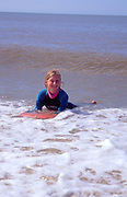 AMHJE3 Girl in wet suit surfing Walberswick beach Suffolk England