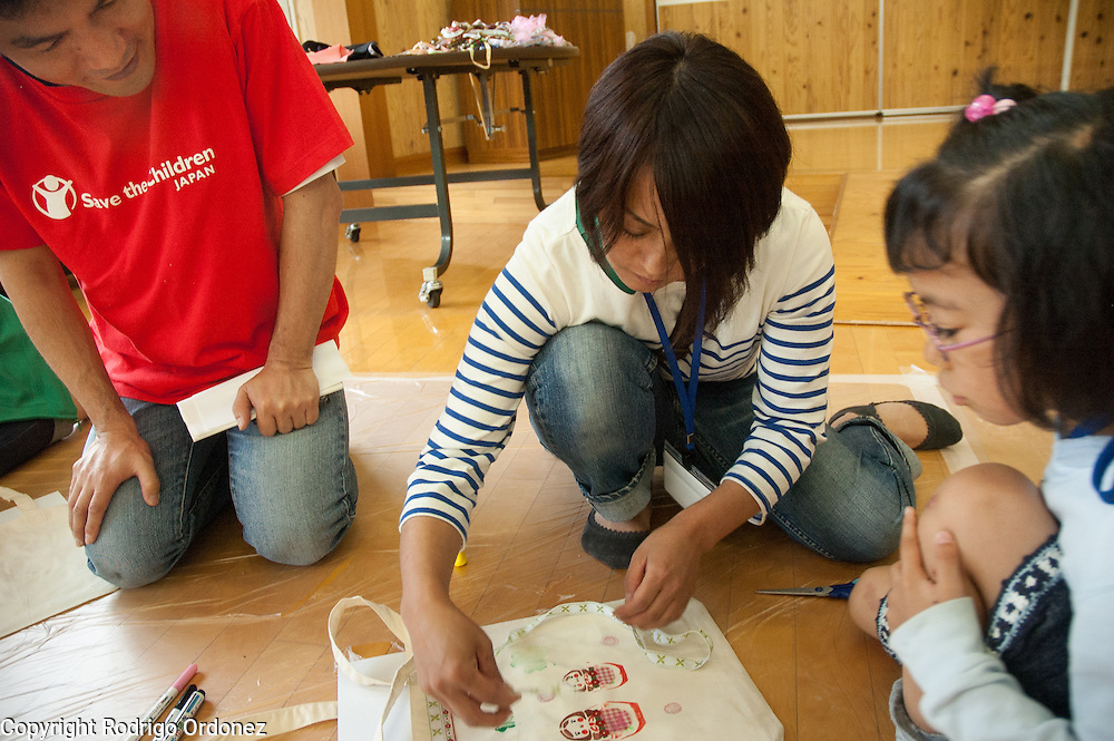 Save the Children staff Hiro Miyashita (left) observes the activities of Kotomi (right) and her mother Noriko Suzuki during a summer camp for children from Fukushima, Japan.