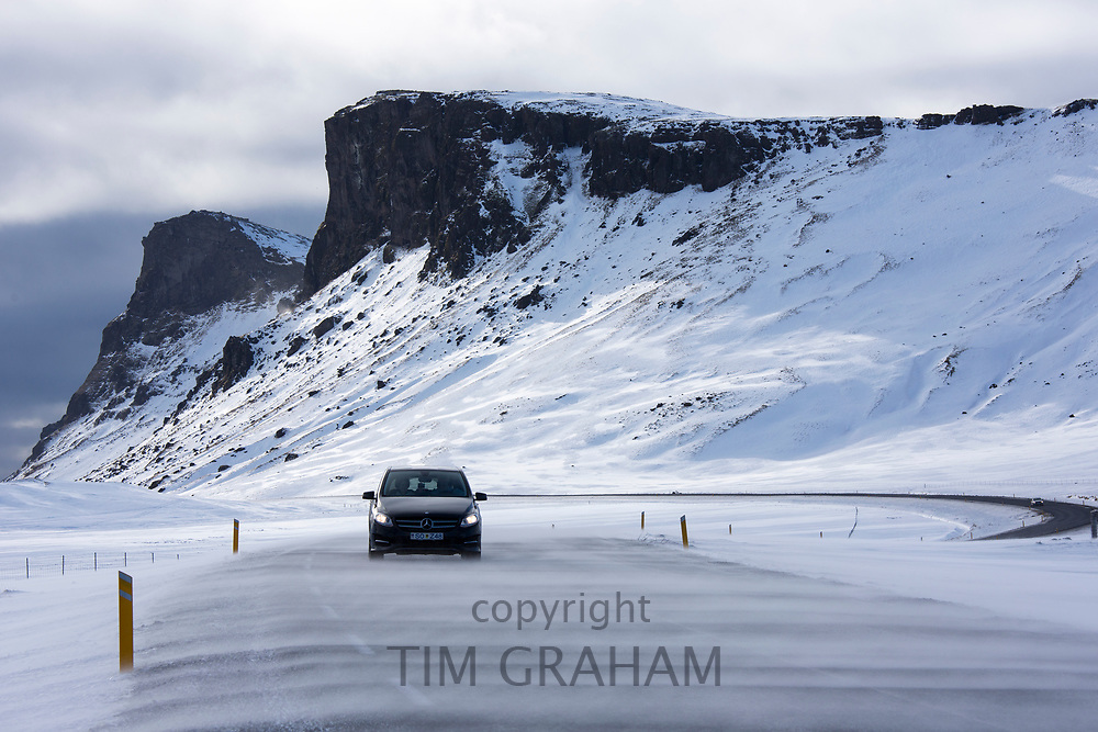 Drifting snow makes motoring conditions difficult  by snow-covered mountains along the main ring road from Reykjavik, South Iceland