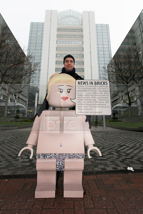 © Licensed to London News Pictures. 26/02/2013. London, UK. Steve Grout, a father of two young boys campaigns with a spoof female Lego model outside The Sun's News International offices in Wapping, East London on 26 February 2013. Demonstrators are calling for Rupert Murdoch to end topless female models in The Sun newspaper, claiming it is unsuitable for family reading and are using a spoof Lego model, nicknamed 'Leanne' as a campaign tool to target the joint promotion running this week between corporate advertisers, Lego and The Sun which is offering free Lego toys aimed at children. Photo credit : Vickie Flores/LNP