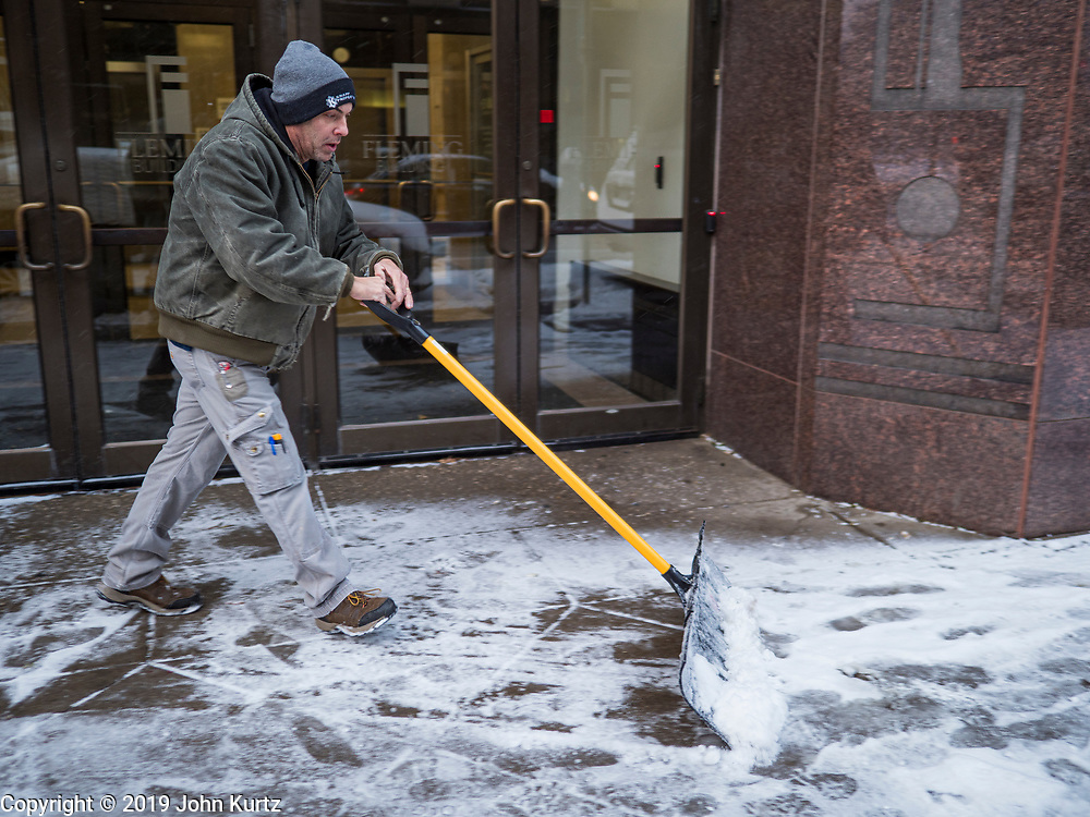 11 NOVEMBERS 2019 - DES MOINES, IOWA: A man shovels snow on a sidewalk in downtown Des Moines. About three inches of snow fell in the Des Moines area Sunday night into Monday morning snarling the Monday morning rush hour and delaying central Iowa schools by about two hours.       PHOTO BY JACK KURTZ