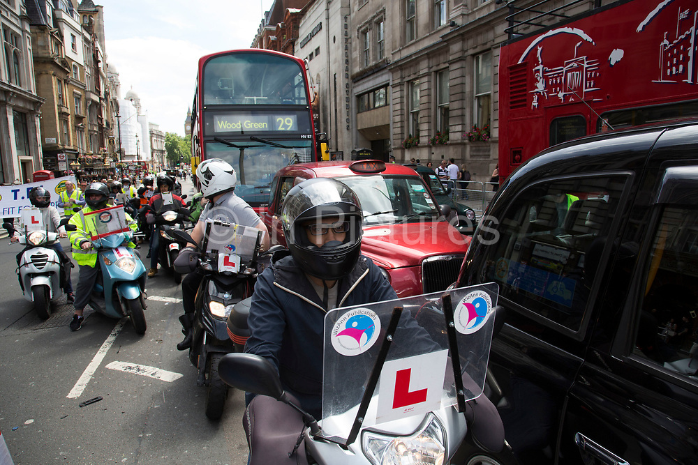 London, UK. Wednesday 11th June 2014. Black taxi drivers protest against taxi service app Uber, brings Whitehall in central London to a standstill. Joined in many numbers by future black cab drivers on mopeds currently doing 'The Knowledge'. London cabbies emphasised that they had no problem with Uber, only with Transport for London for not enforcing current legislation. Taxi drivers say the Uber app is tantamount to a meter and should be regulated like taxi meters. Uber says it has seen an 850% increase in sign-ups compared to last Wednesday and describes the London Taxi Drivers Association (LTDA), as being stuck in the dark ages.