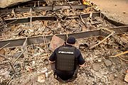 Redding Police Department investigator Rusty Bishop searches a destroyed home along the 11000 block of Quartz Hill Road as they investigate missing person reports during the Carr Fire on Saturday, July 28, 2018, in Redding, Calif. The Carr Fire that burned into Redding grew to 80,900 acres — around 125 square miles — and was only 5 percent contained as of Saturday morning, according to Cal Fire. Two firefighters have died in the blaze.