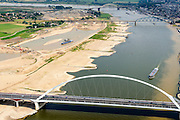 Nederland, Gelderland, Nijmegen, 26-06-2014; de nieuwe stadsbrug van Nijmegen over rivier de Waal, De Oversteek. Daarachter de spoorbrug met fietspad (De Snelbinder) en de laatste brug is de Waalbrug. Links van de rivier grondwerkzaamheden voor de Dijkteruglegging Lent (Ruimte voor de Rivier). Links Nijmegen-Noord, rechts binnenstad.<br /> First bridge the new city bridge of Nijmegen on the river Waal, De Oversteek (The Crossing). Next the railway bridge with cycle path De Snelbinder (The Luggage strap) and finally the Waal bridge. To the left of the river groundwork for the Dike relocation of Lent (project Ruimte voor de Rivier: Room for the River). Nijmegen city on the horizon.luchtfoto (toeslag op standaard tarieven);<br /> aerial photo (additional fee required);<br /> copyright foto/photo Siebe Swart.