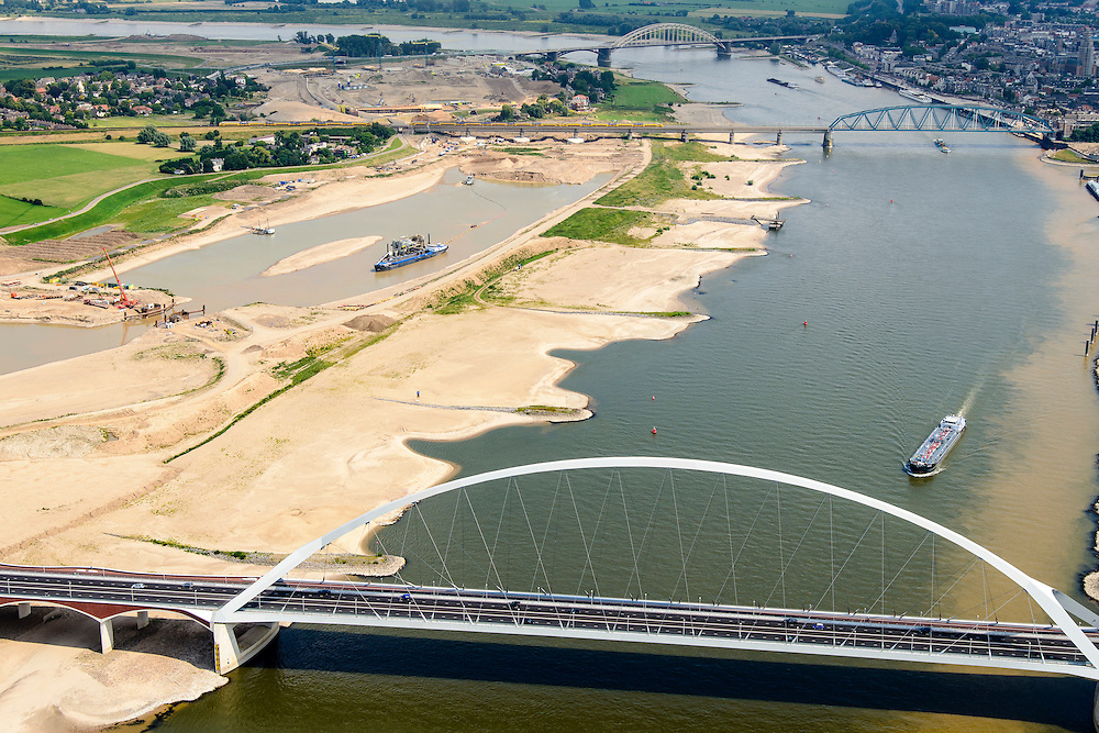 Nederland, Gelderland, Nijmegen, 26-06-2014; de nieuwe stadsbrug van Nijmegen over rivier de Waal, De Oversteek. Daarachter de spoorbrug met fietspad (De Snelbinder) en de laatste brug is de Waalbrug. Links van de rivier grondwerkzaamheden voor de Dijkteruglegging Lent (Ruimte voor de Rivier). Links Nijmegen-Noord, rechts binnenstad.<br /> First bridge the new city bridge of Nijmegen on the river Waal, De Oversteek (The Crossing). Next the railway bridge with cycle path De Snelbinder (The Luggage strap) and finally the Waal bridge. To the left of the river groundwork for the Dike relocation of Lent (project Ruimte voor de Rivier: Room for the River). Nijmegen city on the horizon.luchtfoto (toeslag op standaard tarieven);<br /> aerial photo (additional fee required);<br /> copyright foto/photo Siebe Swart.