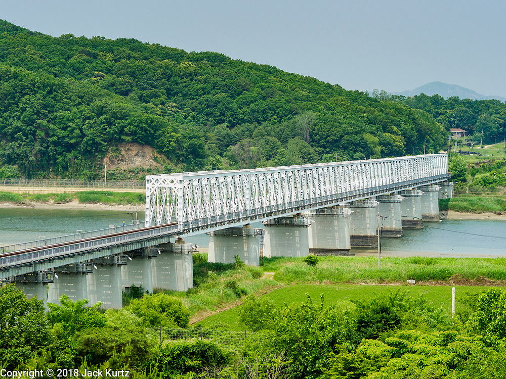 """09 JUNE 2018 - IMJINGAK, PAJU, SOUTH KOREA:  The """"Freedom Bridge"""" from the South Korean side of the Korean DMZ in Imjingak. The bridge, now closed, is called the Freedom Bridge because it is the bridge POWs returning to the South crossed when they were releases by North Korea after the cease fire was signed. The Bridge could be reopened for train traffic if a peace treaty is signed with North Korea. Imjingak is a park and greenspace in South Korea that is farthest north most people can go without military authorization. The park is on the south bank of Imjin River, which separates South Korea from North Korea and is close the industrial park in Kaesong, North Korea that South and North Korea have jointly operated.    PHOTO BY JACK KURTZ"""