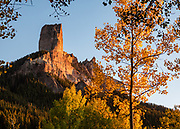 Sunset shines on Chimney Rock (11,781 ft) and Courthouse Mountain (12,152 ft), in the San Juan Mountains, near Ridgway, Colorado, USA. Yellow aspen fall colors were peaking on October 3, 2019. Drive up to Owl Creek Pass at 10,114 feet on the steep Owl Creek-Cimarron Road, an old cattle-drive trail winding through Uncompahgre National Forest.