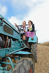 Mature couple driving tractor in cornfield, Bavaria, Germany
