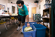 """16 SEPTEMBER 2020 - MITCHELLVILLE, IOWA: CORDELL PACE puts meals into a bin at the Mitchellville Library. Volunteers will deliver the meals to homebound residents of the town. There is no grocery store in Mitchellville, a small community in eastern Polk County. It doesn't qualify as a """"food desert"""" under USDA guidelines because there are grocery stores within 10 miles in neighboring communities, but based on state data, Mitchellville is the poorest community in Polk County (which includes the Des Moines metropolitan area). The Mitchellville zip code has the lowest per capita income in Polk County. Many people don't own cars and can't get to neighboring communities to buy groceries. The library in Mitchellville has made arrangements with a neighboring community to serve hot meals. Every day someone from the Mitchellville library picks up hot meals from a nearby town and distributes them in the library. Heritage Word of Life, a church across the street from Library, has a food pantry in their Fellowship Room where people can pick up fresh vegetables, staples, and hygiene needs.      PHOTO BY JACK KURTZ"""