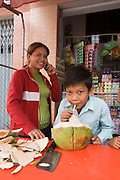 Bunroeun eats a cocunut at a local shop in Phnom Penh..A Khmer boy learns to play classical violin at the college of Beaux Arts, at the edge of Cambodia's capital, Phnom Penh. He is an orphan and comes from a poor family. His parents died long ago, from AIDS related diseases. He lives with his grandmother and his uncle, and their family. He lives on the top floor of an apartment block, where his family run a textile business, sewing together clothes and ornamental flags from around the world. A dozen young women work in this textile business, and the boy's home space is actually amidst this small factory environment which he shares with them. They eat, work and play together like an extended family or community. Phnom Penh, Cambodia