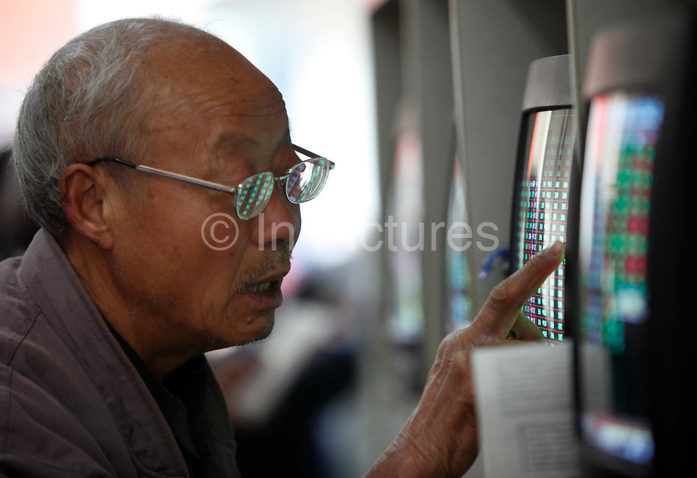 Investors check and trade stocks at a securities exchange house in Shanghai, China on 11 February, 2009.   An elderly investor checks and trades stocks at a securities exchange house in Shanghai, China on 11 February, 2009.