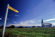 """The old white wooden Church of Raukokore is a unique sight when travelling along the shores of East Cape. On this image, still to be seen with the older sign that points to a """"Historic Church""""."""