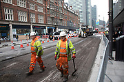 Workmen busy at work resurfacing the street on Tottenham Court Road in London, United Kingdom.