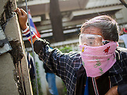 26 DECEMBER 2013 - BANGKOK, THAILAND: An anti-government protestor takes shelter behind a utility pole in front of the Thai Japan Stadium in Bangkok. Thousands of anti-government protestors flooded into the area around the Thai Japan Stadium to try to prevent the drawing of ballot list numbers by the Election Commission, which determines the order in which candidates appear on the ballot of the Feb. 2 election. They were unable to break into the stadium and ballot list draw went as scheduled. The protestors then started throwing rocks and small explosives at police who responded with tear gas and rubber bullets. At least 20 people were hospitalized in the melee and one policeman was reportedly shot by anti-government protestors.      PHOTO BY JACK KURTZ