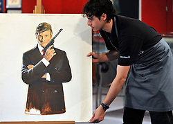 "© licensed to London News Pictures. LONDON, UK.  24/06/11. A Bonhams assistant holds a portrait of Roger Moore, attributed to Robert McGinnis. The artwork is believed to be the original for the poster of ""The Man with the Golden Gun"". It is expected to raise £2000-3000. Photo call for highlights form Bonhams' upcoming Entertainment Memorabilia Sale. .Mandatory Credit Stephen Simpson/LNP"