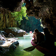People in canoes under the limestone cliffs of the Phang Nga Bay caves, Thailand