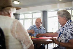 Senior women and man playing ludo board game at rest home, Bavaria, Germany, Europe