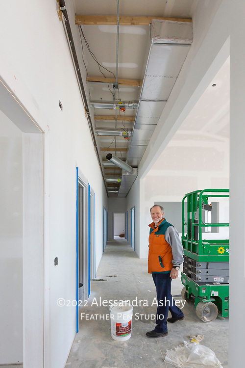Business owner visits building site as wall priming progresses.