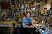 Art restorer Vyacheslav ?Slava? Grankovskiy in his studio workshop behind his home in Shlisselburg, near St. Petersburg, Russia, with his typical day's worth of food. (From the book What I Eat: Around the World in 80 Diets.)  The caloric value of his day's worth of food in the month of October was 3900 kcals. He is 53 years of age; 6 feet, 2 inches tall; and 184 pounds. The son of a Soviet-era collective farm leader, he was raised near the Black Sea and originally worked as an artist and engineer. Over the years, he's learned a few dozen crafts, which eventually enabled him to restore a vast number of objects, build his own house, and be his own boss. His travel adventures have included crossing the Karakum Desert in Turkmenistan, where he spent time with a blind hermit and dined with a Mongol woman who hunted bears and treated him to groundhog soup. His favorite drink: Cognac. Does he ever drink soda? ?No, I use cola in restoration to remove rust, not to drink,? he says. MODEL RELEASED.