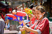 "Apr. 13, 2010 - Bangkok, Thailand: Thais squirt each other with water on Songkran in central Bangkok Tuesday. Songkran is the Thai New Year's holiday, celebrated from April 13 - 15. This year's official celebrations have been cancelled because of the Red Shirt protests but Thais are still marking the holiday. It's one of the most popular holidays in Thailand. Songkran originally was celebrated only in the north of Thailand, and was adapted from the Indian Holi festival. Except the Thais throw water instead of colored powder. The throwing of water originated as a way to pay respect to people, by capturing the water after it had been poured over the Buddhas for cleansing and then using this ""blessed"" water to give good fortune to elders and family by gently pouring it on the shoulder. Among young people the holiday evolved to include dousing strangers with water to relieve the heat, since April is the hottest month in Thailand (temperatures can rise to over 100°F or 40°C on some days). This has further evolved into water fights and splashing water over people riding in vehicles. The water is meant as a symbol of washing all of the bad away and is sometimes filled with fragrant herbs when celebrated in the traditional manner. Photo by Jack Kurtz"