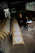 Woman preparing rice-paper in traditional method. The wet rice-paper sheets are placed on woven bamboo frames which are then placed in the sun to dry..Rice-paper is used in many traditional Vietnamese dishes, especially Vietnamese spring rolls. Rice-paper is also cut into strips and becomes rice-noodles. Cu Chi, Vietnam