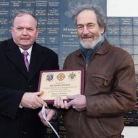 An tUachtaran Cumann Luthchleas Gael, Mr. Liam O'Neill, presents an award to local artist, Richard Sharpe, who painted the murals at Kilmurry Ibreckane GAA pitch.