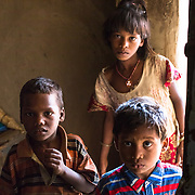 CAPTION: Wide-eyed children strain their eyes in the dark to see who's come to visit their home. LOCATION: Singhilpur, Saran District, Bihar, India. INDIVIDUAL(S) PHOTOGRAPHED: Unknown.