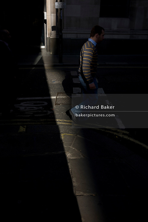 A man wearing a striped jumper walks through a shaft of early spring light in a side street in the capital's financial district. This is Lombard Street, originally a piece of land granted by King Edward I to goldsmiths from the part of northern Italy known as Lombardy (larger than the modern region of Lombardy). It is a narrow and usually dark sidestreet near the Bank of England in the heart of what is called the Square Mile - the inner-part and oldest quarter of London occupied first by the Romans 2,000 years ago. Nowadays the City of London is home to banks and financial institutions but also with a resident population of under 10,000 but a daily working population of 311,000.