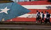 School children walk past a Puerto Rican flag painted along an embankment in Mayaguez Puerto Rico