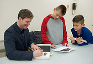 Merrick, New York, U.S.  December 20, 2019.  L-R, author KEVIN SHINICK signs his novel as the brothers RICHIE STRAUS, 10, and STEVEN STRAUS, 9, of West Babylon, look on, at book signing for Shinick's STAR WARS: FORCE COLLECTOR at North Merrick Library on Nassau County Force Collector Day. Author Shinick named home planet of Karr Nuq Sin, the main character of this official canon Star Wars young adult novel, MEROKIA in honor of Merokee tribe who settled his Merrick hometown on Long Island.