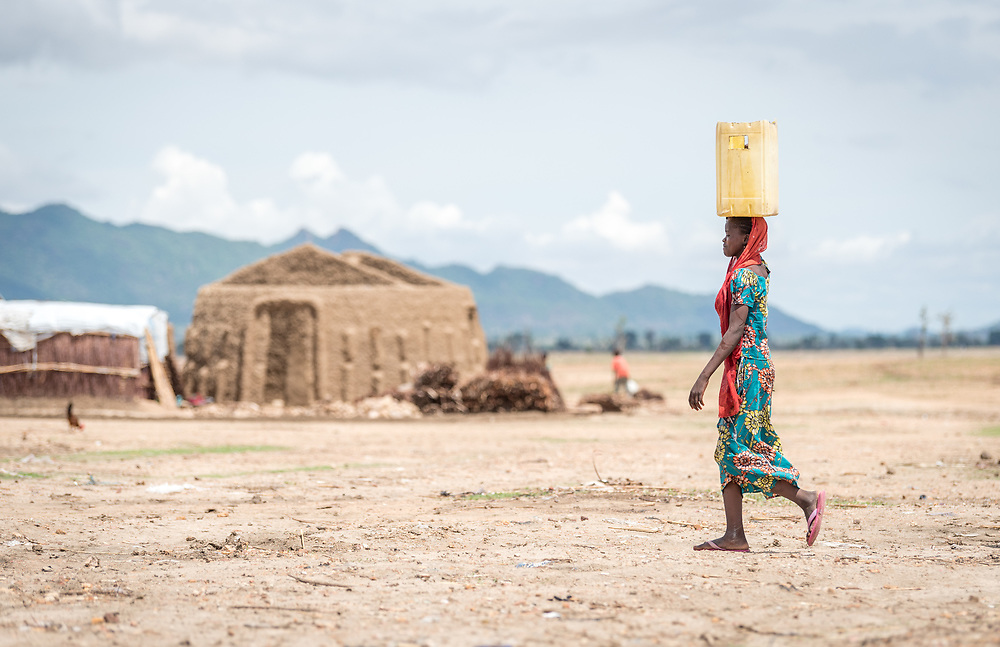 30 May 2019, Mokolo, Cameroon: A woman carries her jerry can through the Minawao camp for Nigerian refugees. The Minawao camp for Nigerian refugees, located in the Far North region of Cameroon, hosts some 58,000 refugees from North East Nigeria. The refugees are supported by the Lutheran World Federation, together with a range of partners.