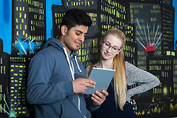 University students with digital tablet in front of graffiti wall School, Bavaria, Germany