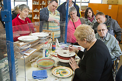 Visually impaired people with carers on outing to Denby Pottery. Demonstration of hand-painting of glaze.