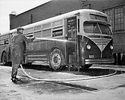 Y-480722B-04.  Worker hosing out debris in bus. 900 bus victim of Vanport flood. Before restoration. Detail shots. Cleaning, paint shop. July  22, 1948