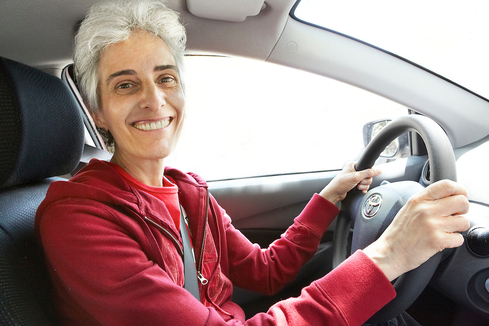 Portrait photograph of smiling woman with short white hair driving Toyota car