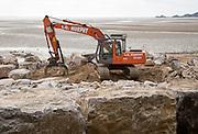 Machinery building rock armour coastal defences at Swansea, West Glamorgan, Wales, UK