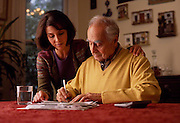 A woman looks over her father as he pays his bills at the kitchen table