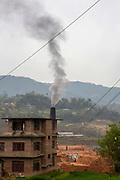 Smoke bellows across the valley from the chimney of a brick kiln on the 11th of March 2020 in the Dakshinkali area, Kathmandu District, Bagmati Pradesh, Nepal. Traditional brick kilns continue to pollute air, take life and cause huge financial loss to Nepal.