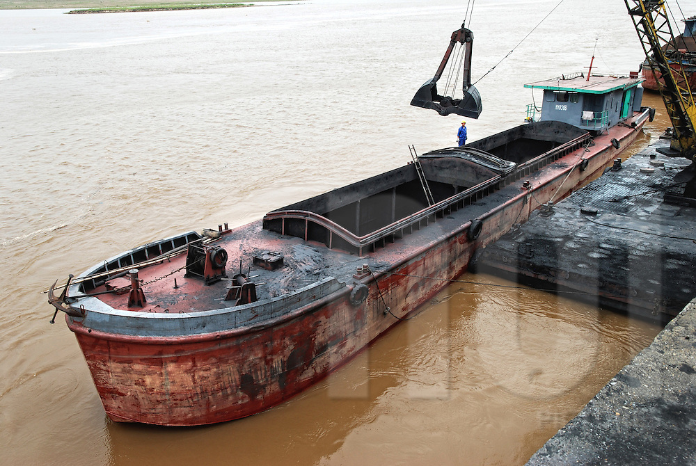 A crane unloads charcoal from a boat in a harbour along the red river, Hanoi, Vietnam, Asia