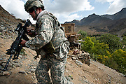 An American soldier scales a rocky slope while conducting a search of nearby houses.