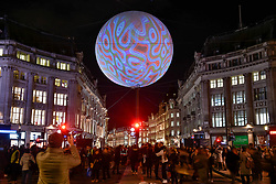 """© Licensed to London News Pictures. 19/01/2018. LONDON, UK.  """"Origin of the World Bubble"""" by Miguel Chevalier, a giant balloon, suspended above Oxford Circus, is illuminated for the first time.  Lumiere London, the capital's largest arts festival commissioned by The Mayor of London and produced by Artichoke.  Light installations by leading artists have been set up, both north and south of the river for the public to view 18-21 January.  Photo credit: Stephen Chung/LNP"""