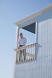 handsome man on a second floor balcony of a wooden home