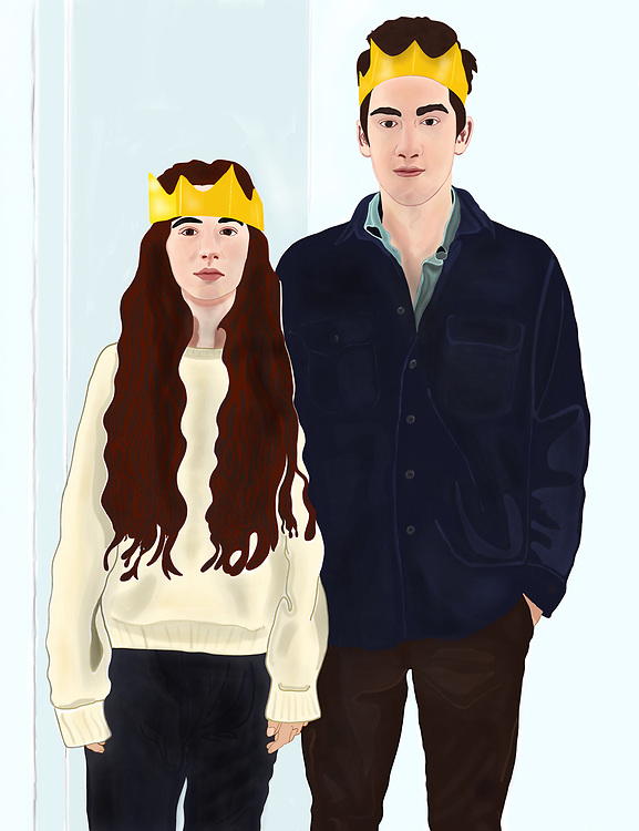 Young girl and boy wearing gold foil paper crowns on New Year's eve.