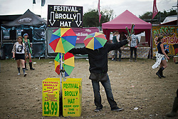 © London News Pictures. 24/08/2012. London, UK. A 'Festival Brolly Hat' sellers face covered by his brolly hat as he tries to sell hats on day one of Reading Festival 2012 in Reading, Berkshire, UK on August 24, 2012. The three day event which attracts over 80,000 music fans opens officially today (Friday) and will headline The Cure, Kasabian and The Foo Fighters Photo credit : Ben Cawthra/LNP